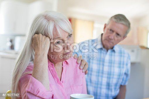 874789476istockphoto Mature Man Comforting Woman With Depression At Home 827627742