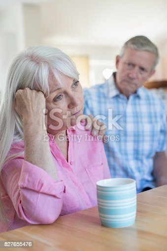 874789476istockphoto Mature Man Comforting Woman With Depression At Home 827655476