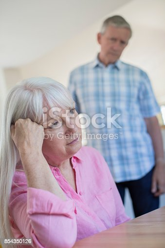 874789476istockphoto Mature Man Comforting Woman With Depression At Home 854350126