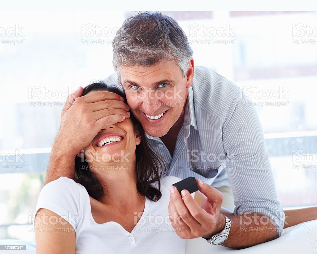 Mature man covering his wife's eyes to surprise her with a ring royalty-free stock photo