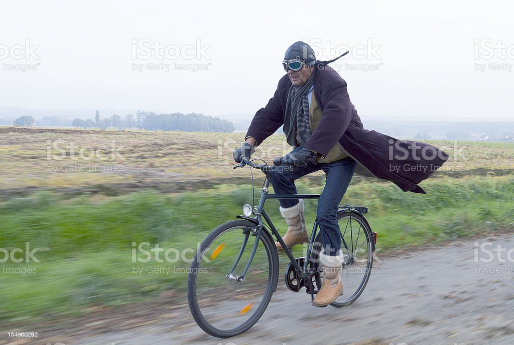 Mature man cycling full speed countryside royalty-free stock photo