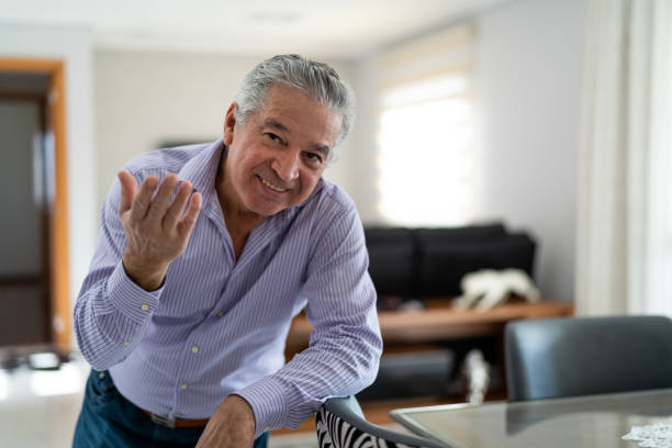Mature Man Dancing and Welcoming Home Opening His Front Door stock photo
