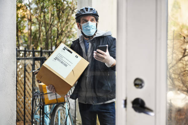 mature man delivering parcel with contactless payment - essential workers stock pictures, royalty-free photos & images