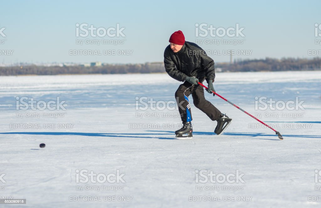 Mature man desperately trying to catch up the pack while playing hockey on a frozen river Dnepr in Ukraine stock photo