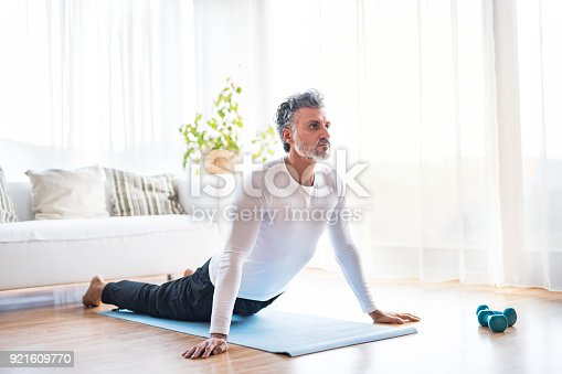 530281733istockphoto A mature man doing exercise at home. 921609770