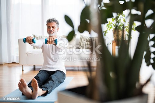530281733istockphoto A mature man doing exercise at home. 921609908