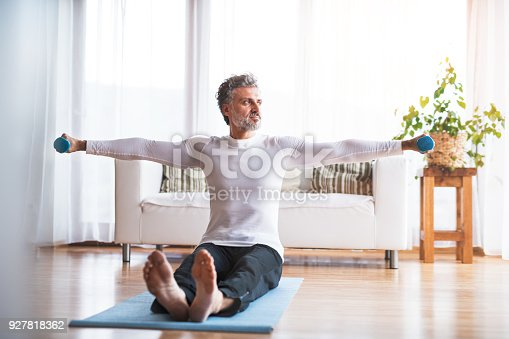 530281733istockphoto A mature man doing exercise at home. 927818362