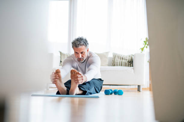 A mature man doing exercise at home. stock photo