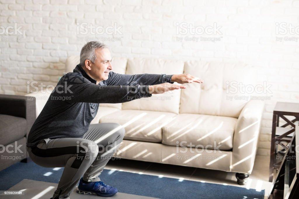 Homme mature faire des squats d'entraînement à la maison - Photo