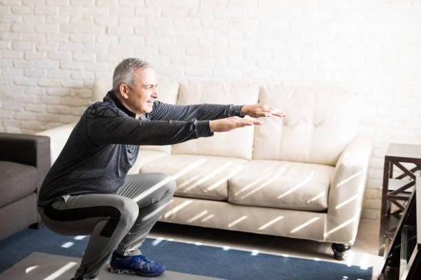 hombre maduro haciendo sentadillas entrenamiento en casa - agacharse fotografías e imágenes de stock