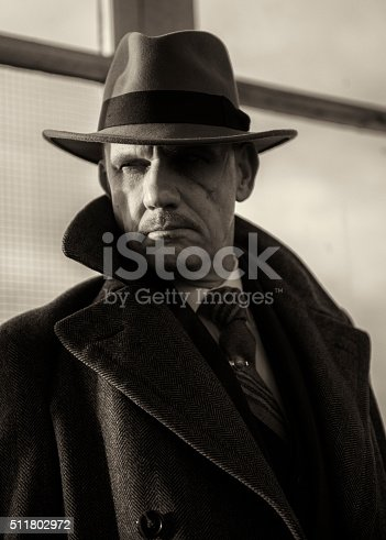 Black and white portrait image of a mature man dressed as a 1940s gangster character.