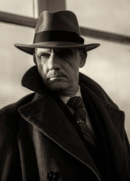 mature man dressed as a 1940s gangster character. - 1920s style stock photos and pictures