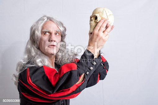 Mature man dressed as Hamlet holding a skull