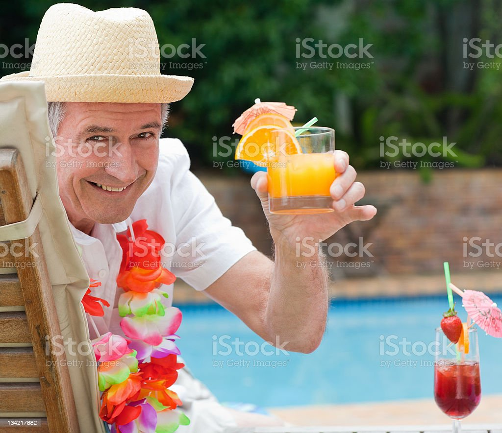 Mature man drinking a cocktail royalty-free stock photo
