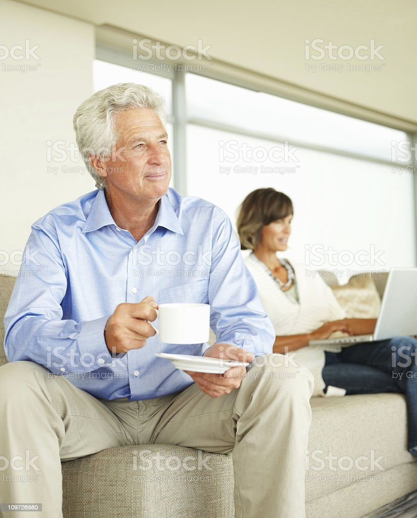 Mature man drinking coffee and woman using laptop royalty-free stock photo