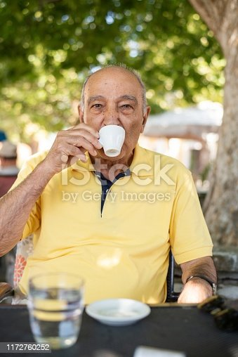 A man in his 70s enjoying an espresso while sitting under a tree in the summer.