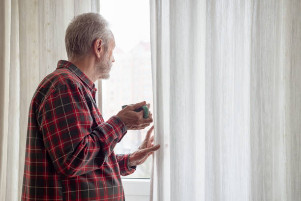 Mature man drinking his coffee and looking out of the window stock photo