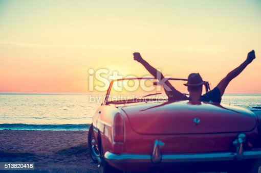 istock Mature man driving a convertible car at the beach. 513820418