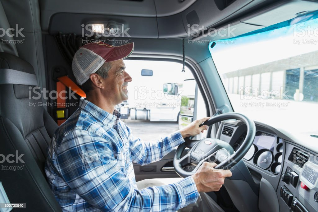 Mature man driving a truck outside warehouse stock photo