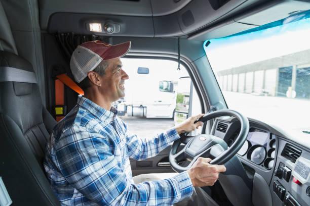 Mature man driving a truck outside warehouse stock photo