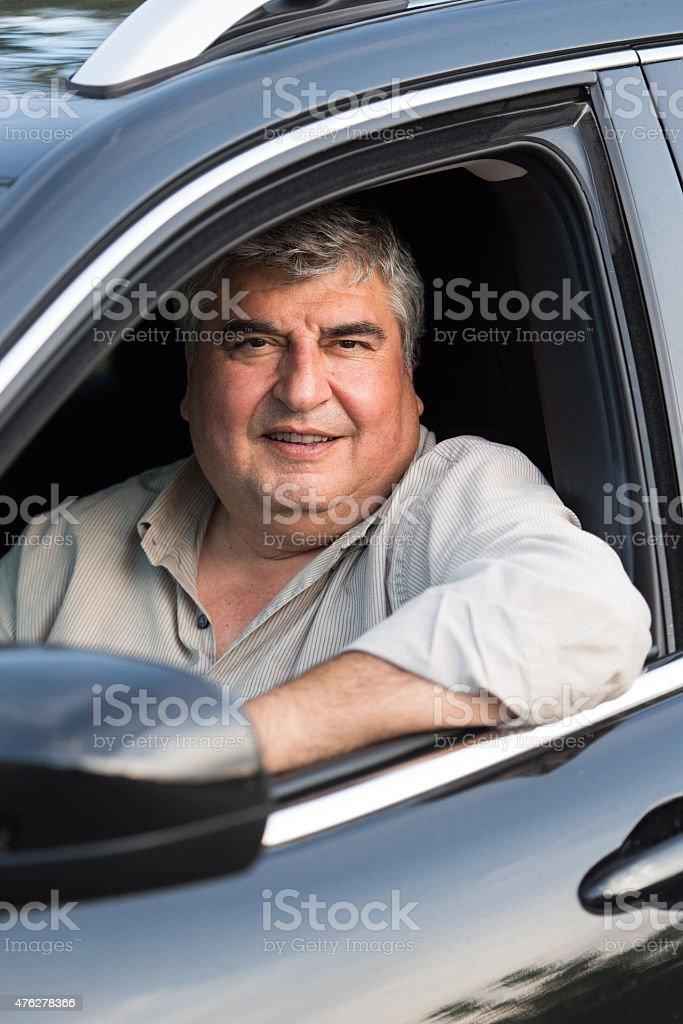 Mature man driving his car stock photo