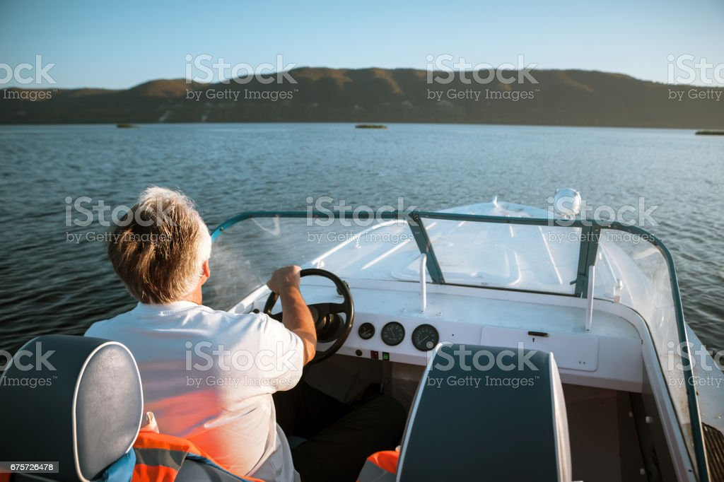 mature man driving speedboat stock photo
