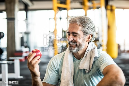 Mature man eating an apple in a gym.