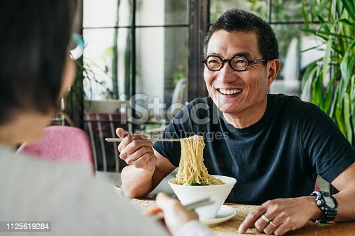 Man in his 50s talking to woman and smiling, freshly made Chinese food, noodle soup, lunch, relaxation