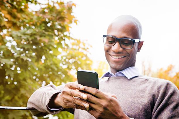 Mature man enjoying social networking on mobile phone stock photo