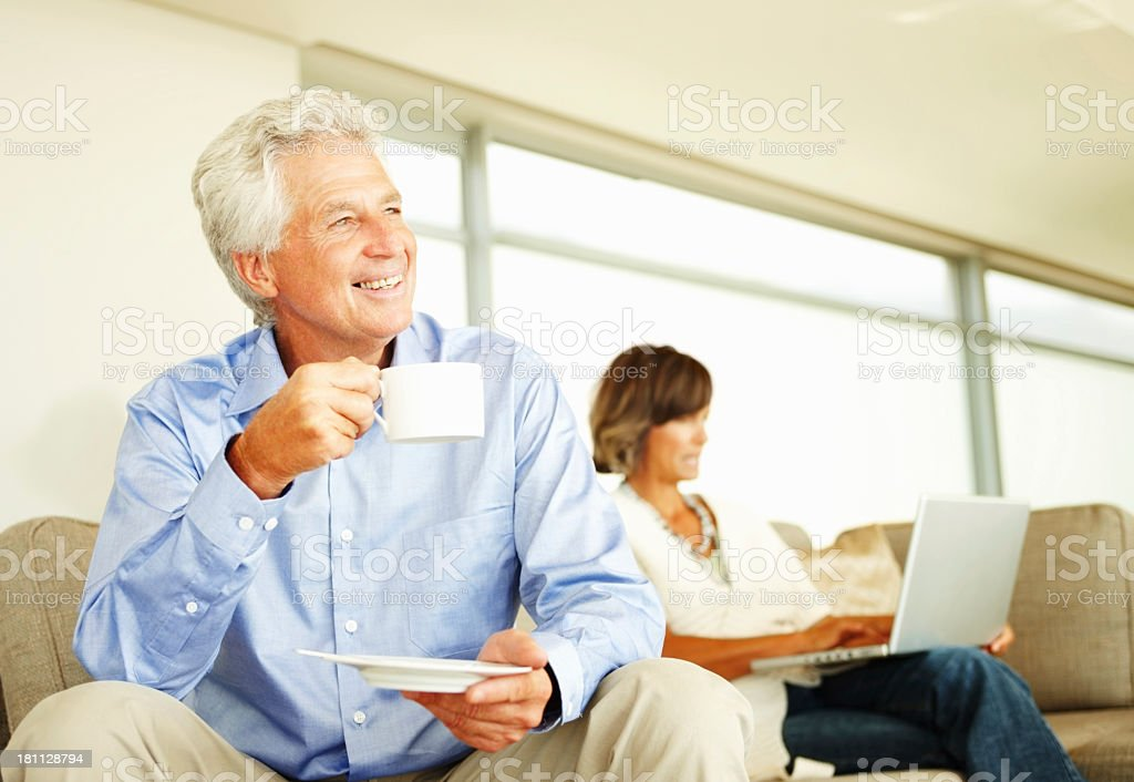 Mature man enjoys a cup of coffee as woman works behind him royalty-free stock photo