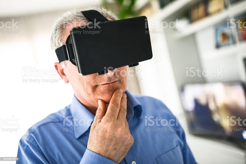 mature man entartains his self with virtual reality device simulator stock photo