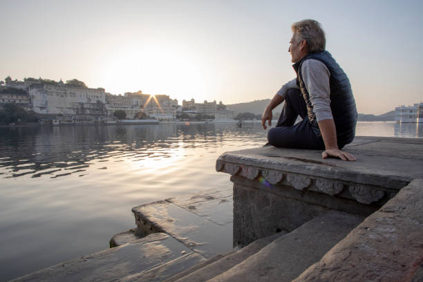 Mature man explores a ghat at sunrise, looks out across lake Lake Pichola, Udaipur lake pichola stock pictures, royalty-free photos & images