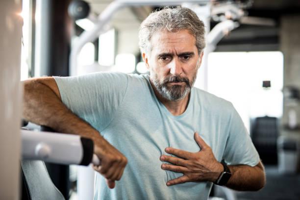 mogen man känsla bröstsmärtor medan du tränar i ett gym. - matsmältningsbesvär bildbanksfoton och bilder