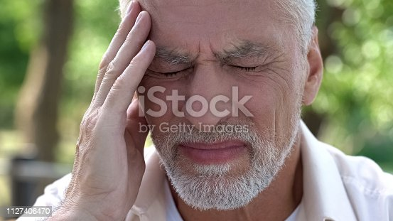 istock Mature man feeling sudden sharp pain in head, migraine attack, risk of thrombus 1127406470