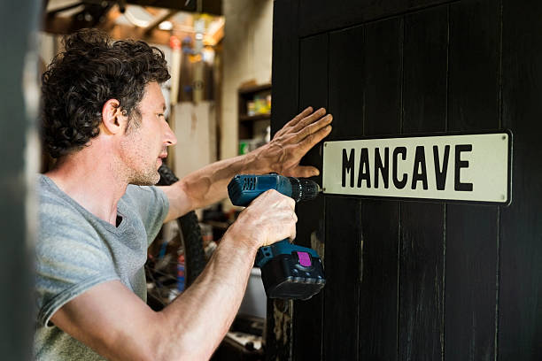 Mature man fixing mancave sign on wooden door Mature man fixing mancave sign on wooden door. Male repairman using power tool. He is working at workshop. man cave stock pictures, royalty-free photos & images