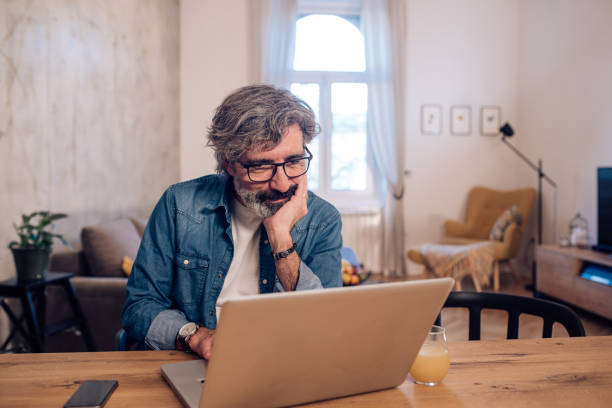 Mature man freelancing from home during the COVID-19 lockdown stock photo