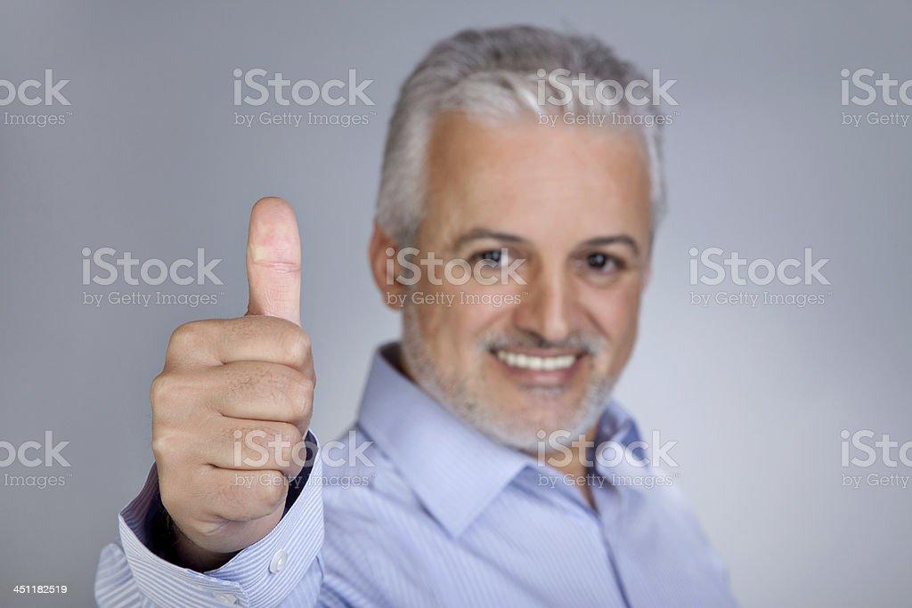 Mature man gesturing thumbs up royalty-free stock photo