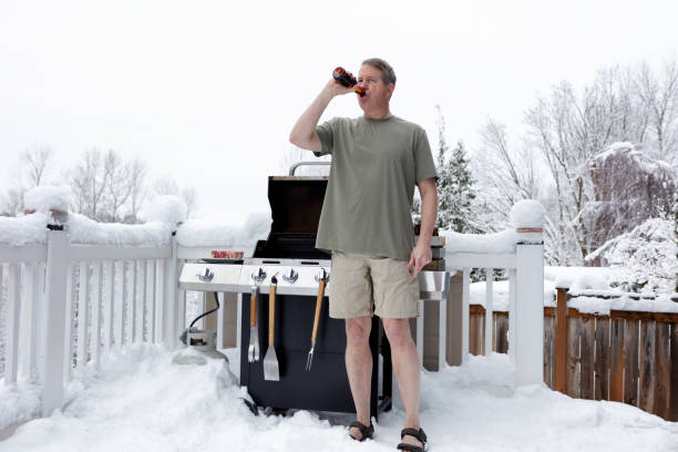 Mature man getting ready to grill while drinking beer during winter season Mature man drinking beer while preparing to barbecue during winter season shorts stock pictures, royalty-free photos & images
