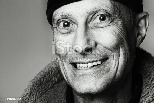 Black and white portrait of a mature man, grinning bizarrely.