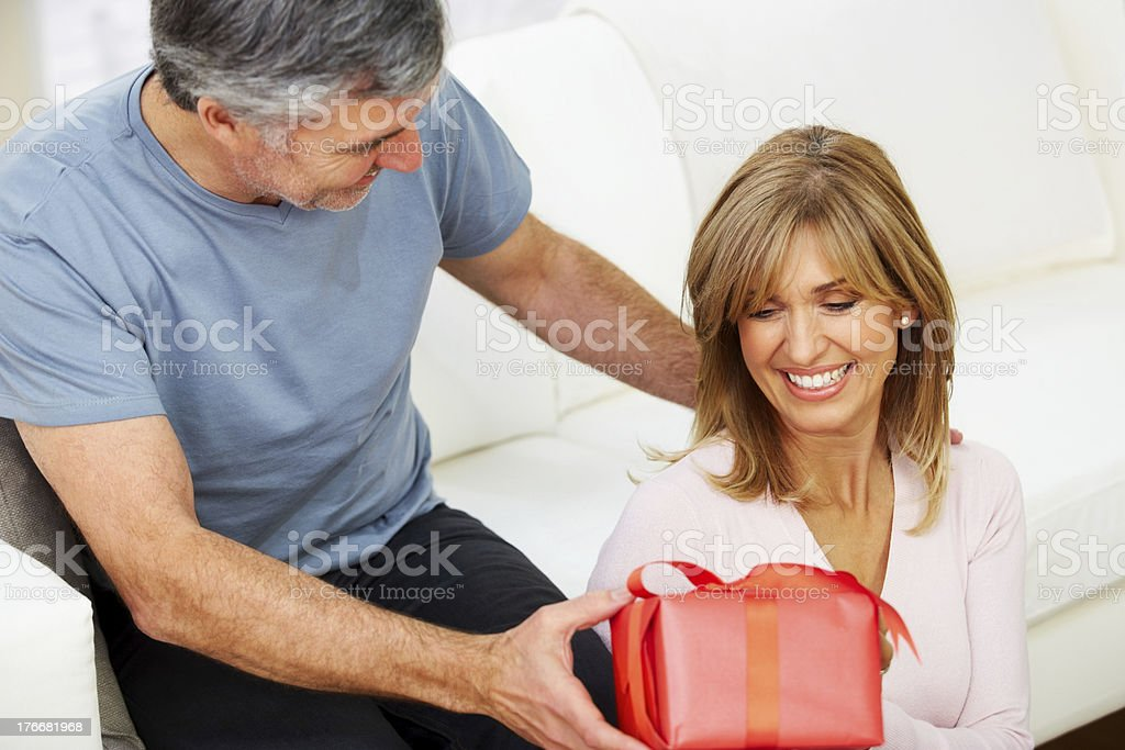 Mature man giving present to his happy wife royalty-free stock photo