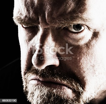 A middle-aged, bearded man glares and glowers at the camera in a threatening manner.