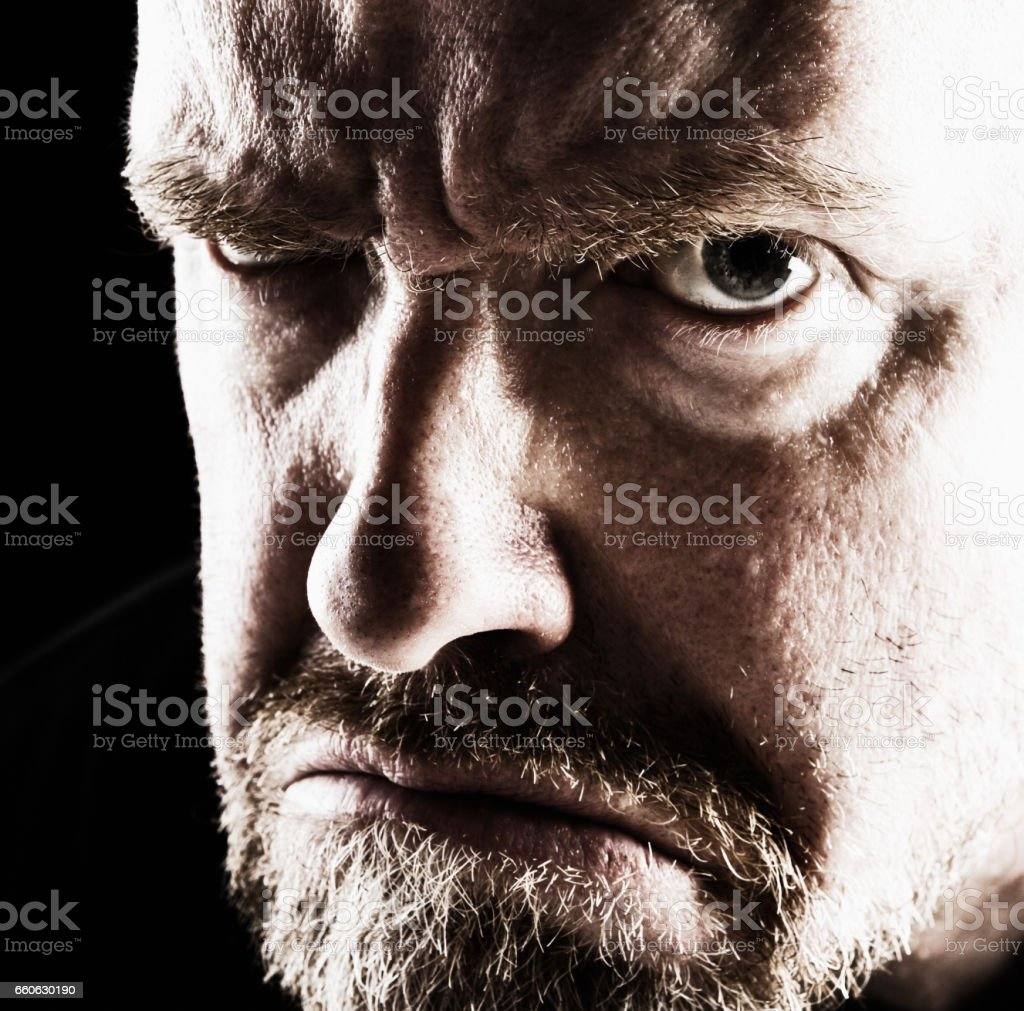 Mature man glares angrily, looking frightening stock photo