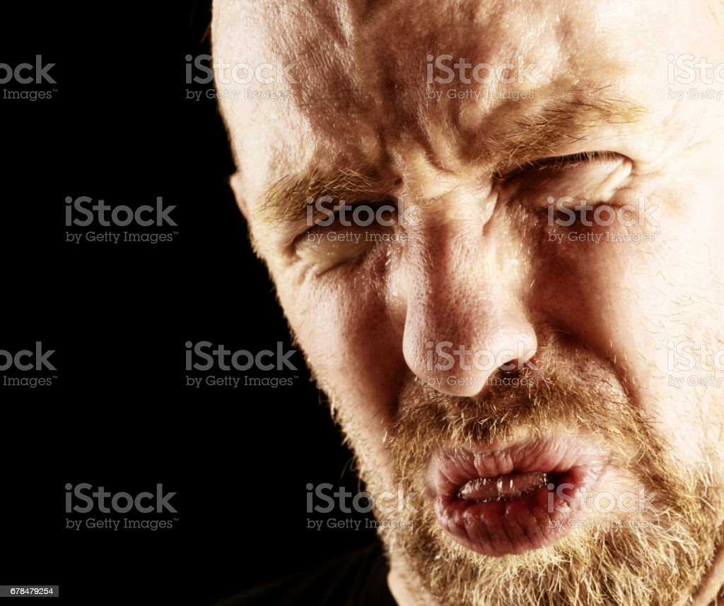 Mature man grimaces in revulsion at something bad tasting stock photo