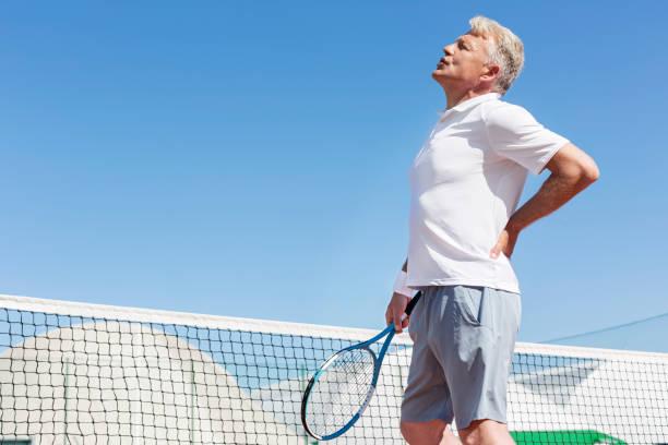 Hombre maduro que muecas con dolor de espalda mientras que sostiene raqueta de tenis contra el cielo azul claro en el día soleado - foto de stock