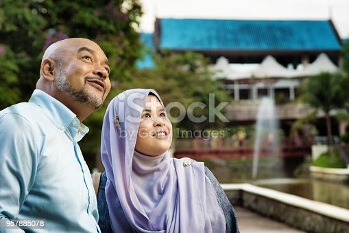 Mature man guiding Female Muslim friend in Kuala Lumpur. They are both looking at the sights, smiling.