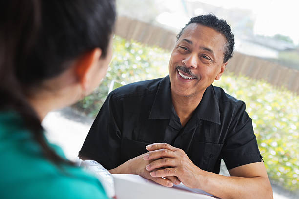 mature man happily talking to healthcare professional about medication - question mark asking doctor nurse stock photos and pictures