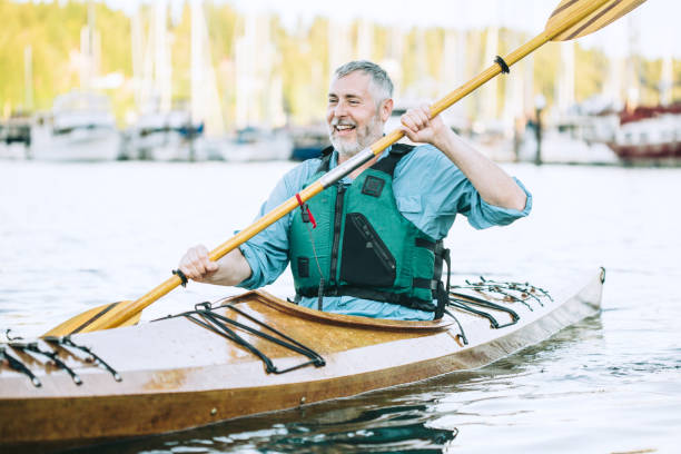Mature Man Has Fun Kayaking Seniors taking on the world!  A mature man is his late 50's enjoys paddling his kayaks on a relaxing vacation in Gig Harbor, Washington, the sun shining on the water of the Puget Sound. gig harbor stock pictures, royalty-free photos & images