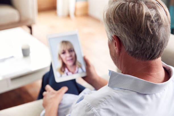 Hombre maduro que tiene consulta en línea con la doctora en casa en la tableta digital - foto de stock