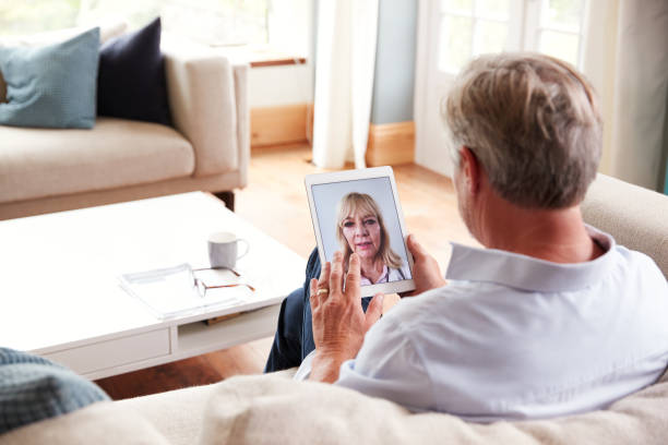 Mature Man Having Online Consultation With Female Doctor At Home On Digital Tablet stock photo