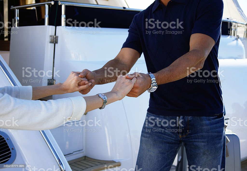 Mature man helping mature woman board yacht, mid section  40-44 Years Stock Photo